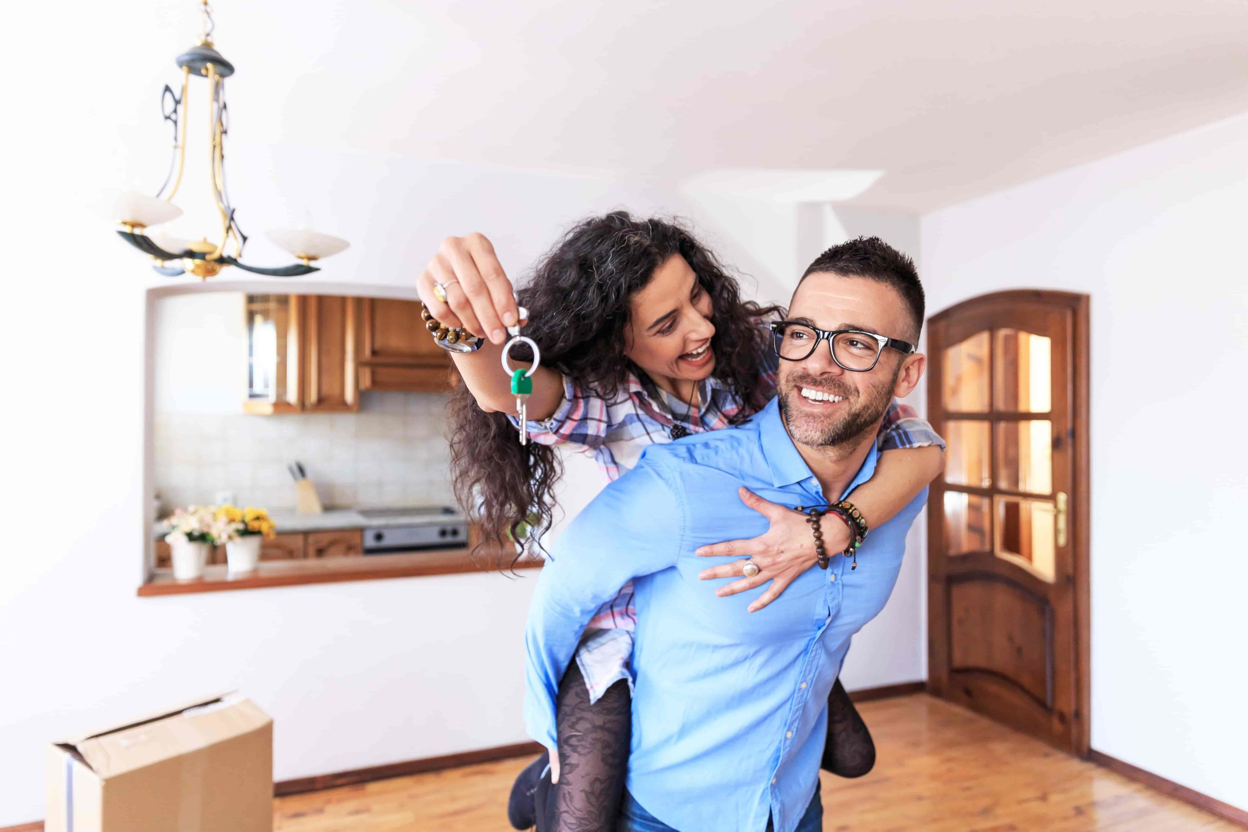 man gives his partner a piggyback ride in their new living room, showing off the keys to new house bought by house hacking