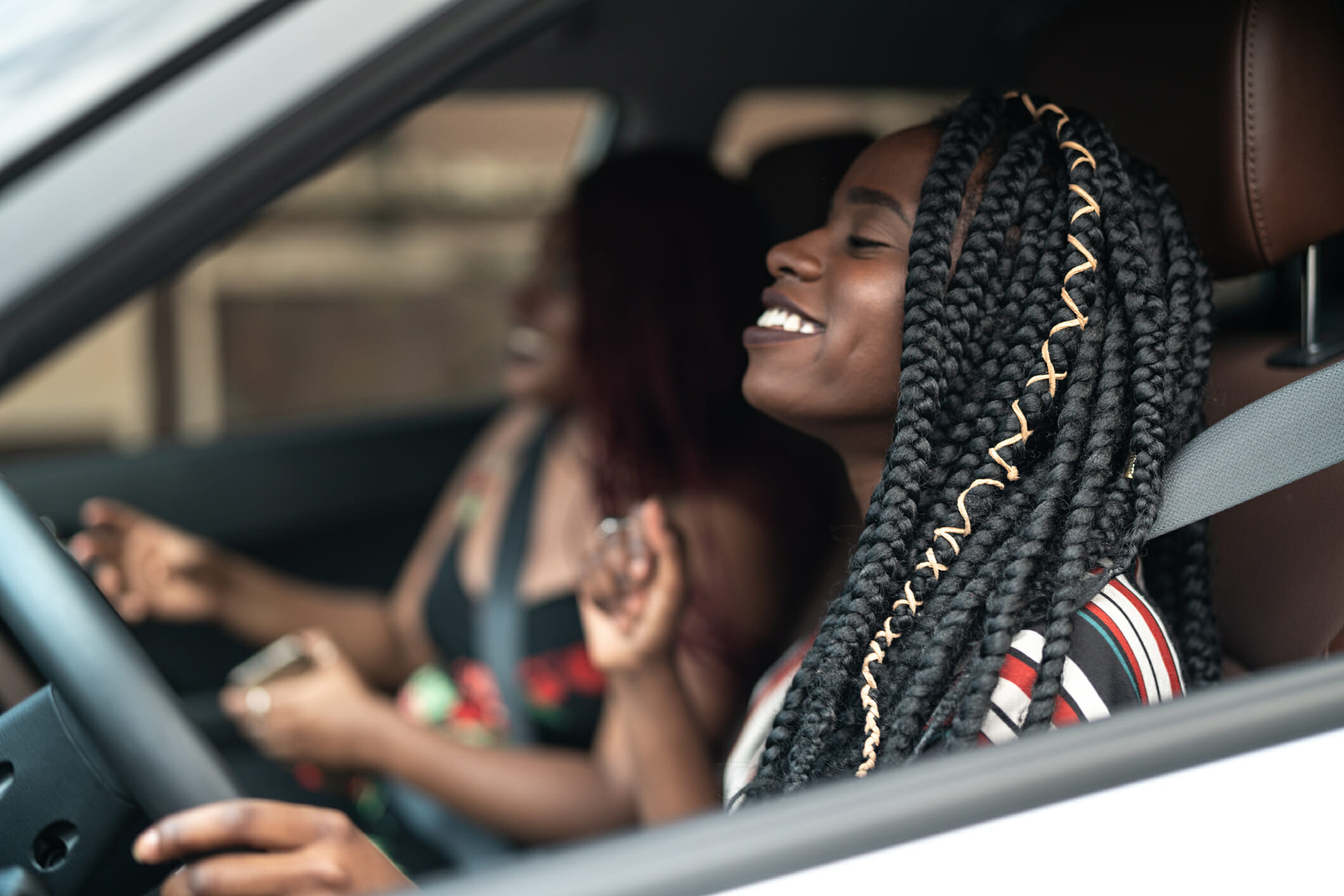 Woman with braids takes her friend for a ride in her new car bought with a credit card