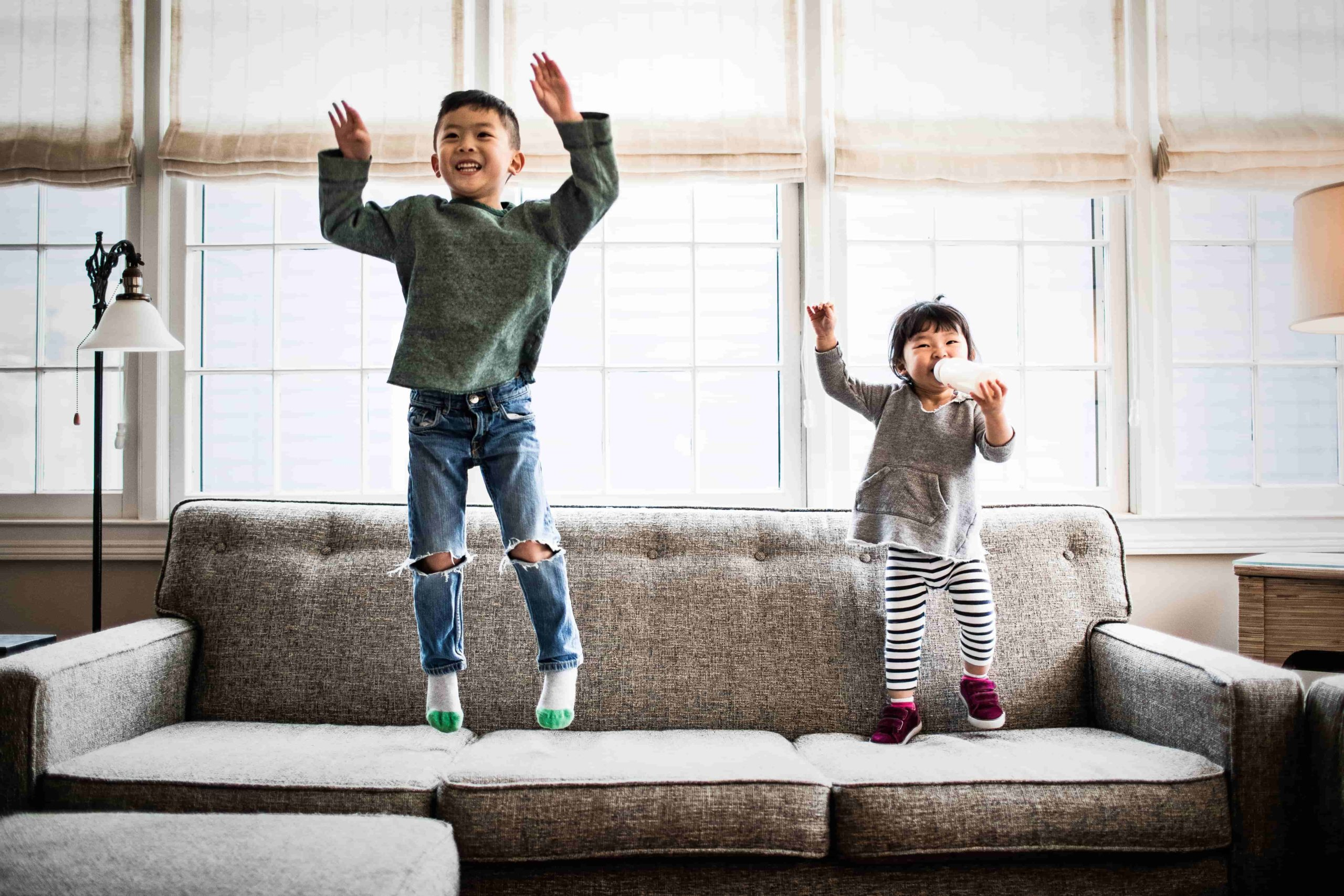 young boy and little sister laugh and bounce on a gray couch in the living room