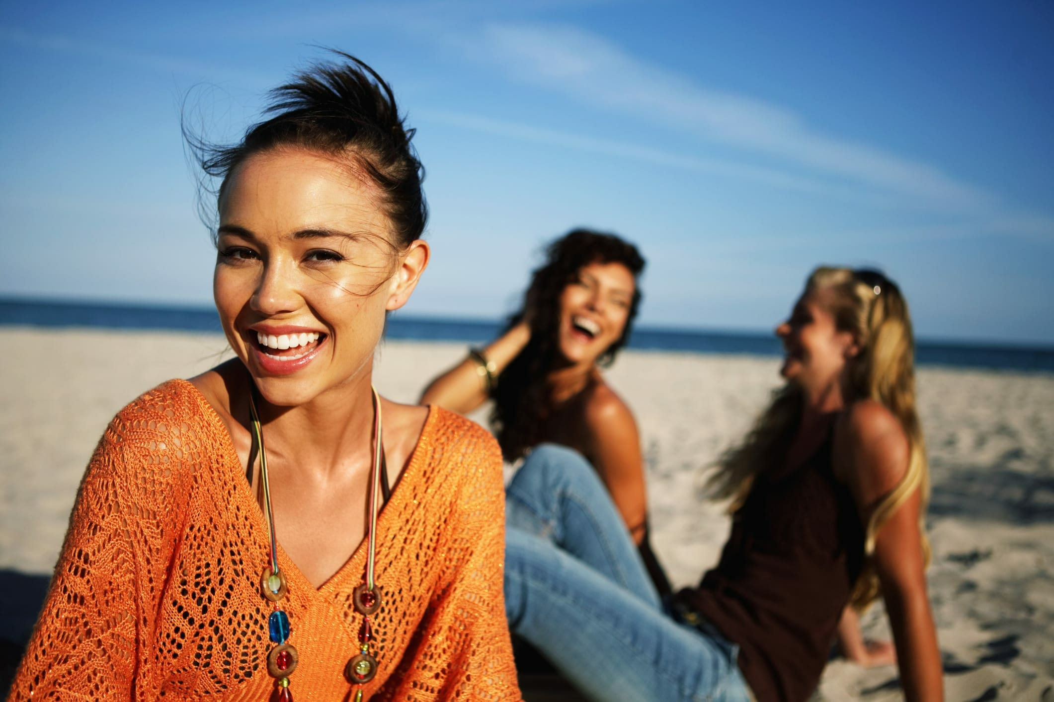 smiling woman in orange at the beach relaxing with friends who made the decision to rent vs. buy a house