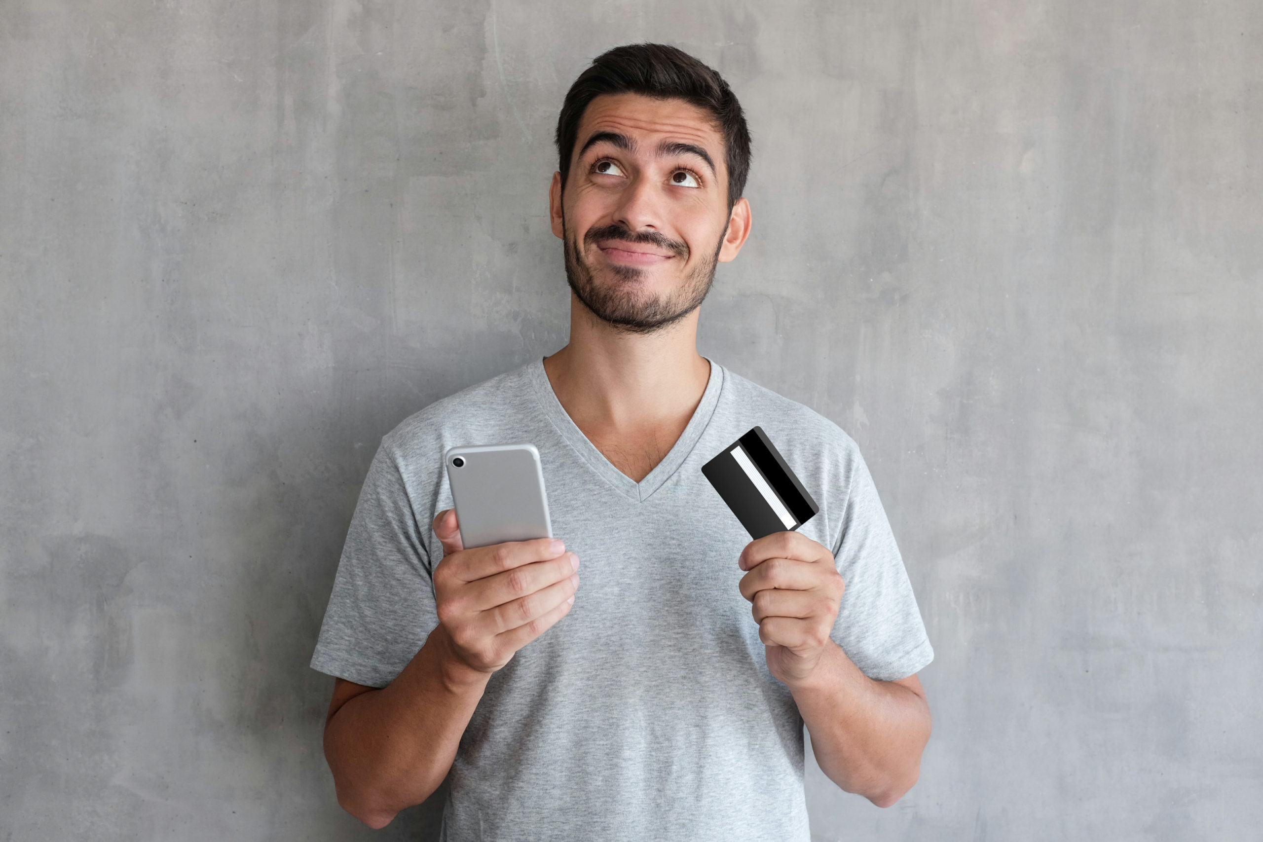 Young man thinking about online shopping via internet, wearing gray t shirt, standing against textured wall, holding credit card and cell phone