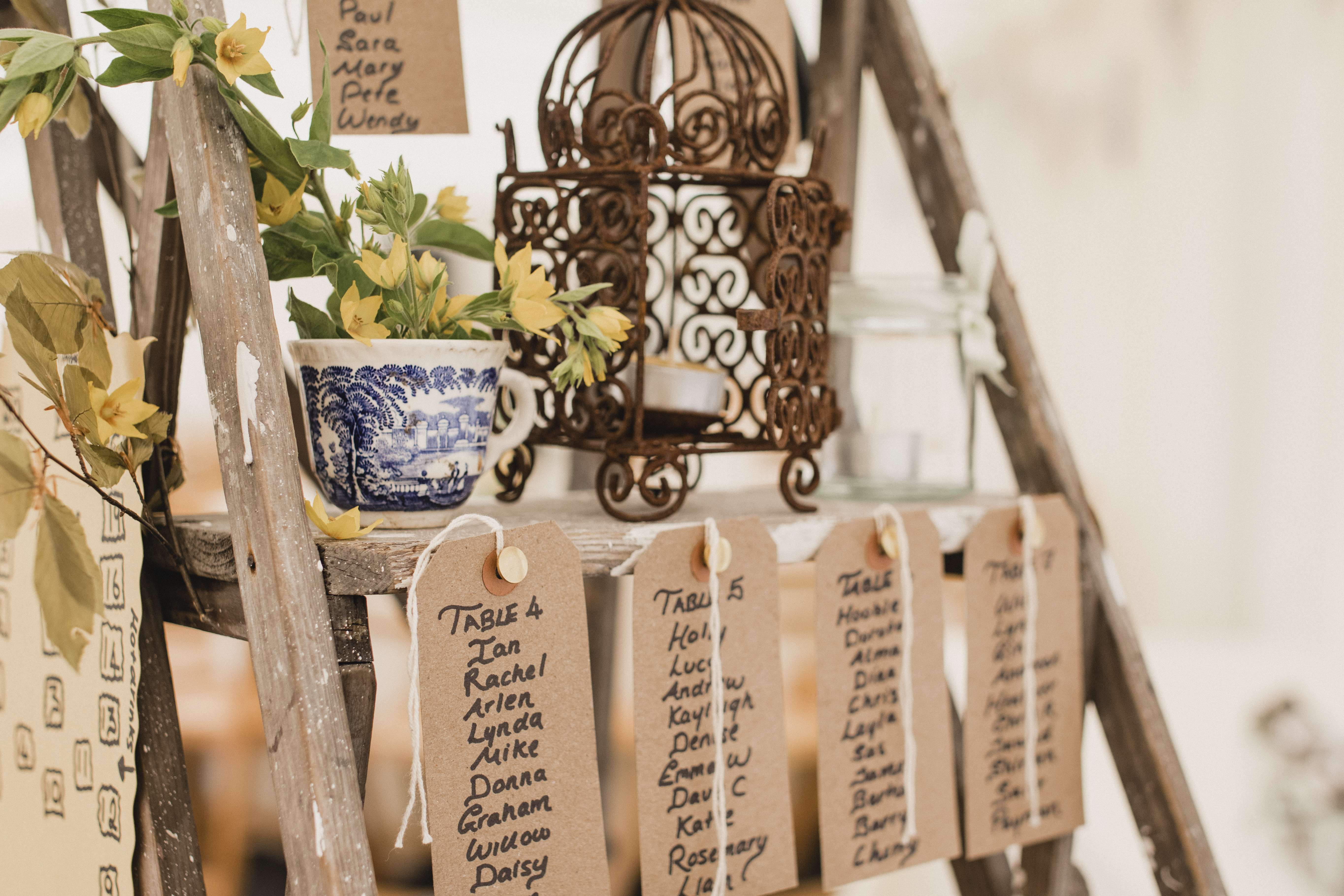A close-up shot of a wooden step ladder at a wedding venue, place cards can be seen with a list of all the wedding guests and a seating plan.
