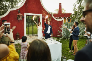 Bride and groom celebrating with sparklers after cutting cake during outdoor wedding reception