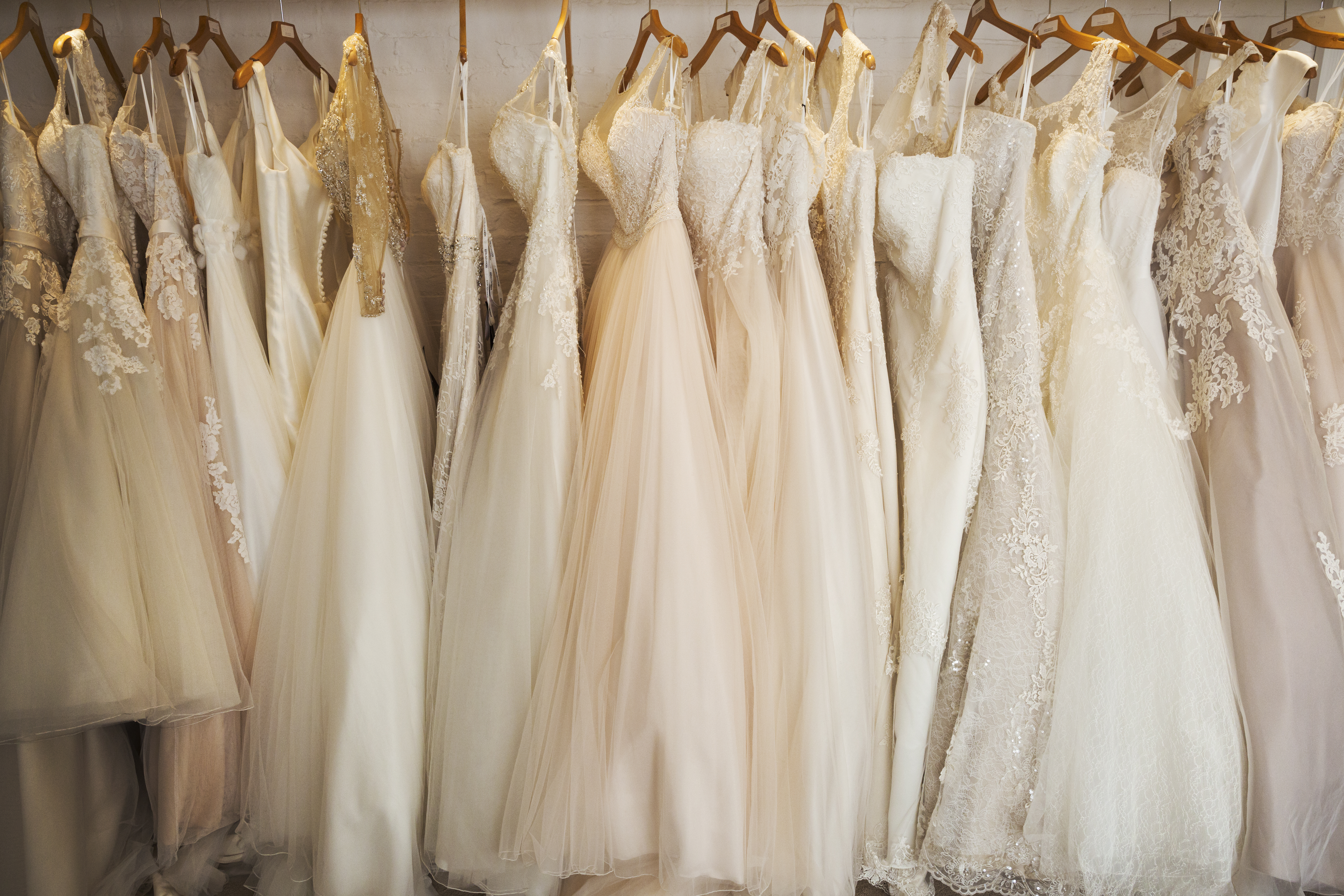 A row of wedding dresses at a wedding shop.