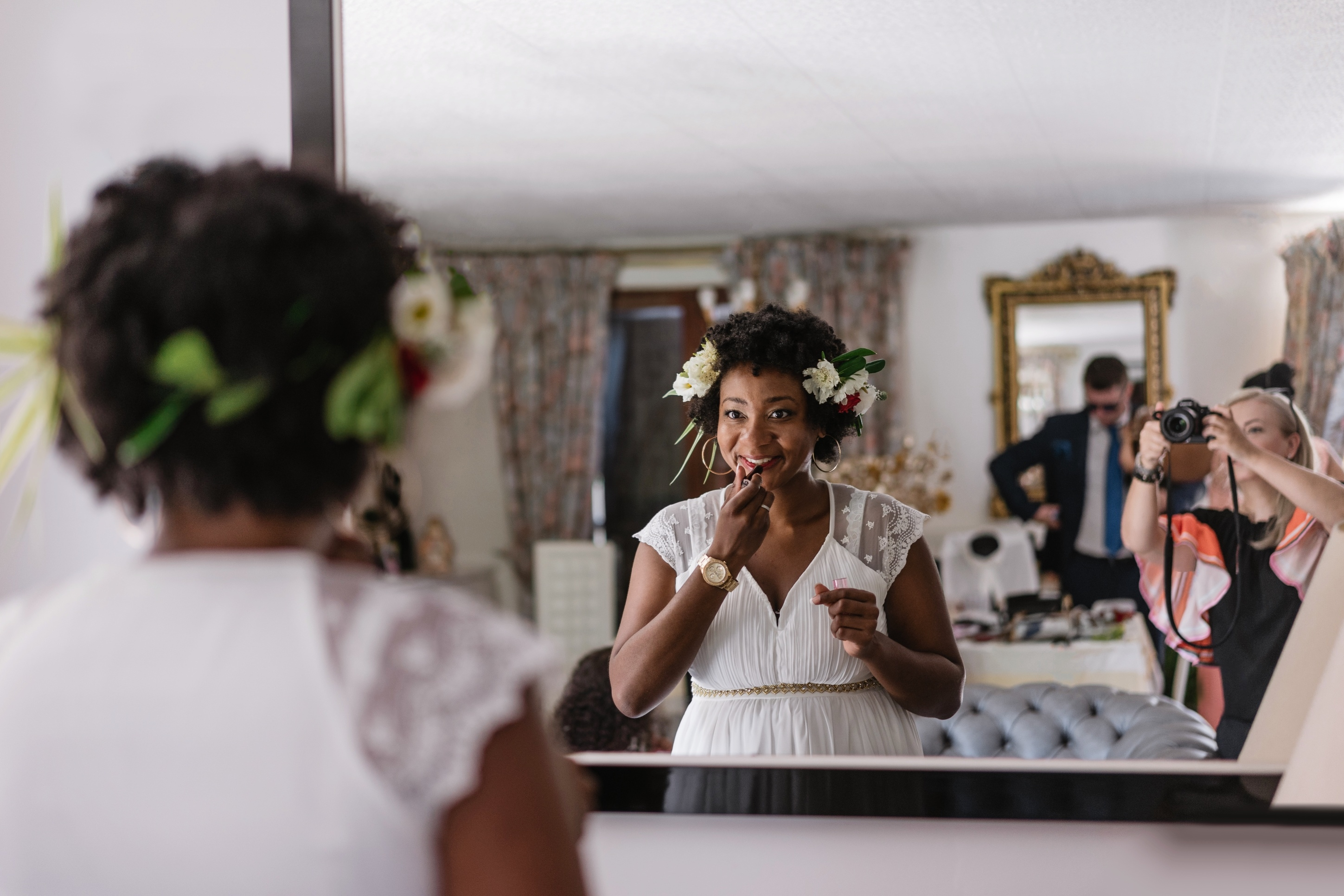 Reflection Of Bride Applying Lipstick While Standing In Front Of Mirror