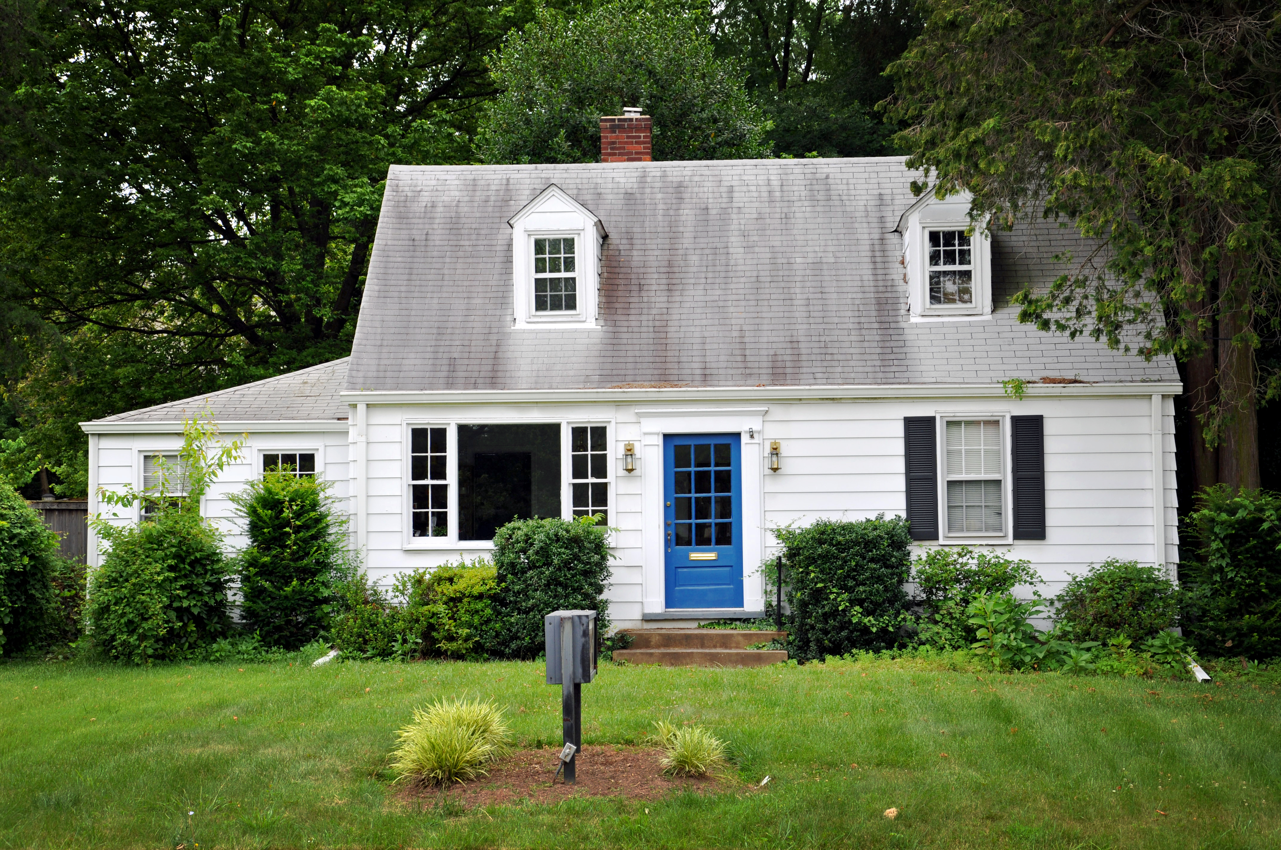 Fixer upper house that is white with a blue door