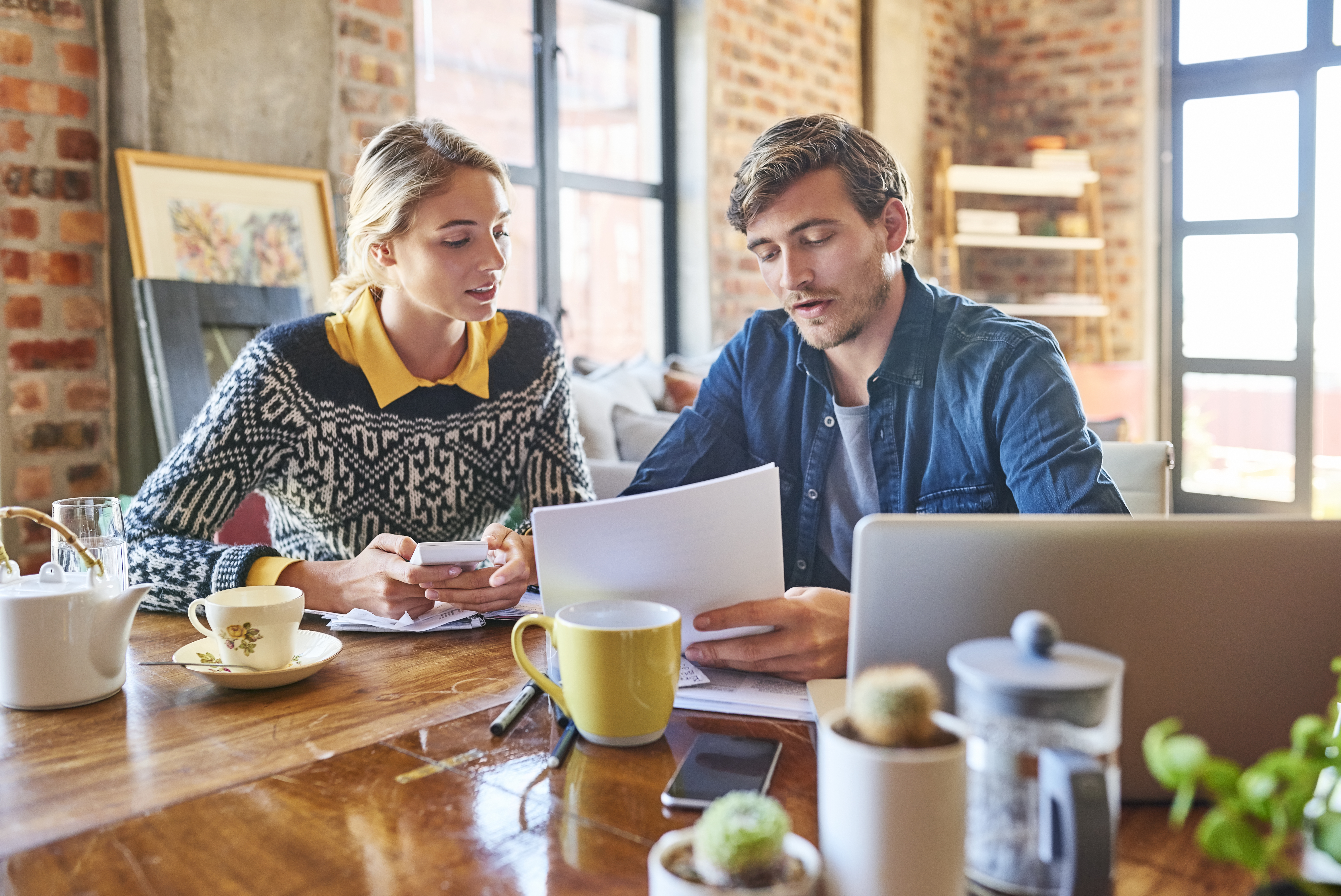Young man and woman calculating home finance. Male and female partners are doing paperwork at table. They are wearing casuals at home.