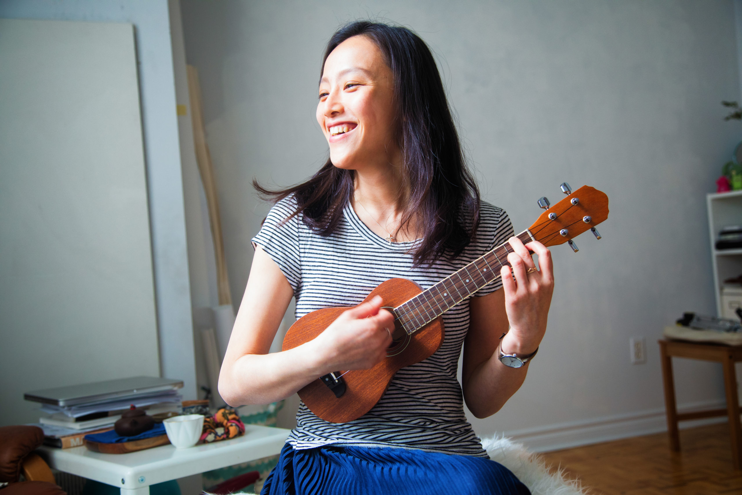 Millennial young Asian woman having fun strumming her Ukulele in her studio apartment, smiling in abandonment.
