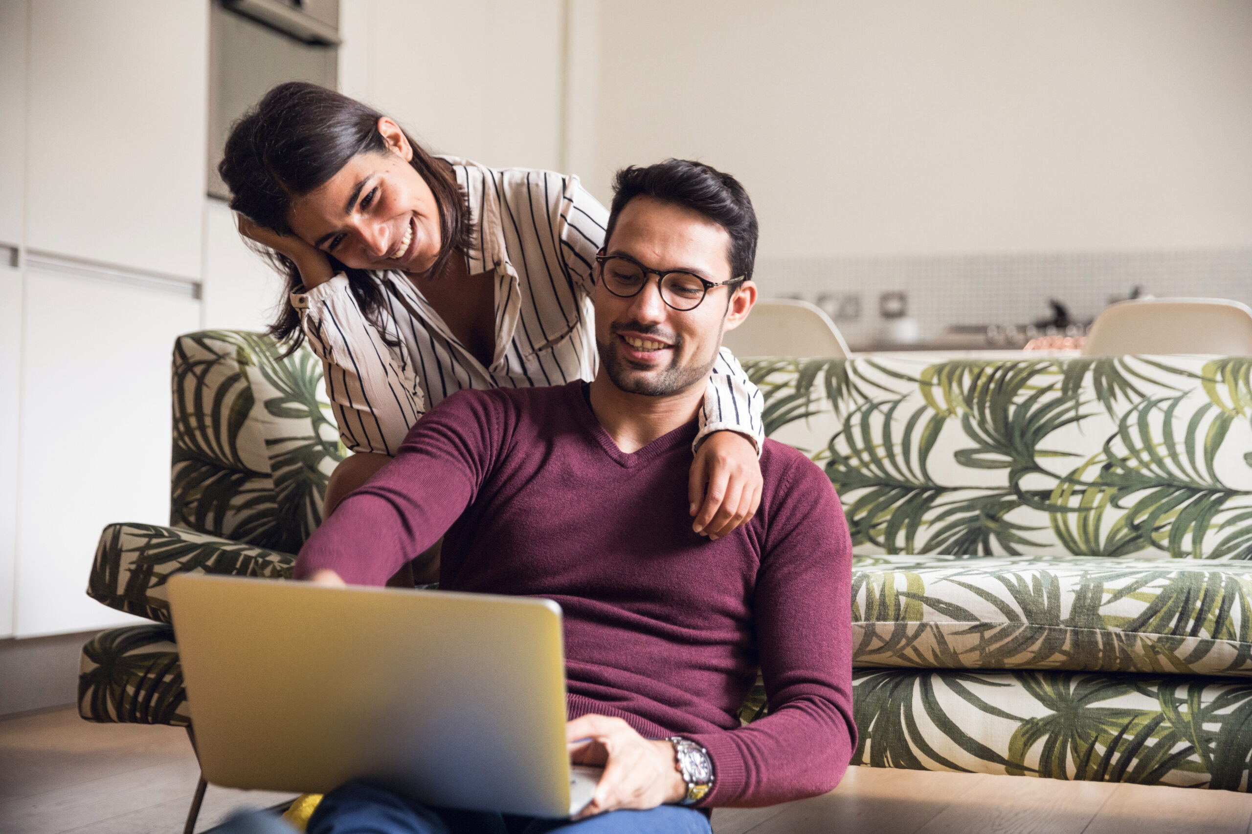 happy couple reviewing real estate offer letter on their laptop
