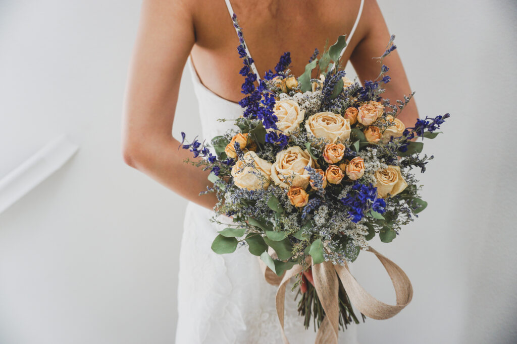 a bride holding a bouquet of dried flowers